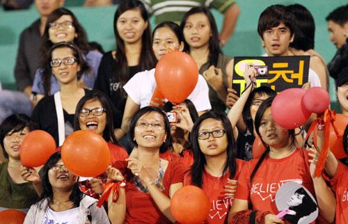 Nhóm fan nữ mặc đồng phục cùng bóng và hoa.