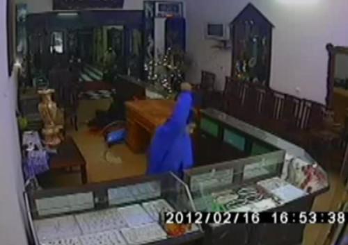 Trong khi bà chủ cửa hàng ngồi hô hoán, tên cướp vẫn đập phá tủ kính để lấy vàng.