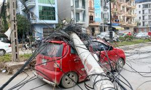 Cột điện đổ trúng ôtô đang đi trên đường