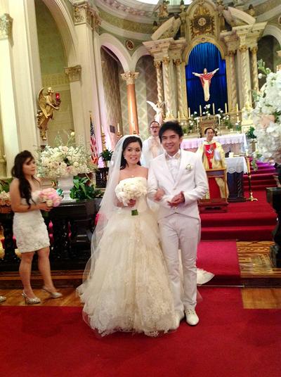 Váy cưới của vợ Đan Trường có phần đắp ren tinh tế ở phía trước, kết hợp cùng voan dài. Đây được xem là phiên bản màu trắng của một thiết kế trong bộ sưu tập Xuân 2013 của nhà thiết kế Vera Wang.