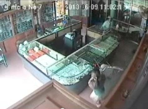 Người phụ nữ trông tiệm vàng nhanh trí dùng ghế che chắn rồi chạy ra ngoài nhờ người giúp. Ảnh cắt từ clip