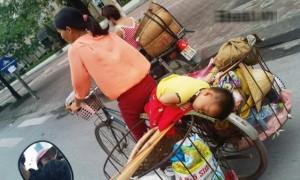 Em bé ngủ gật trên xe đạp cà tàng của mẹ