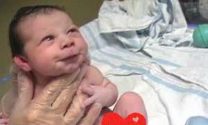 Em bé toét miệng cười với bố khi vừa chào đời