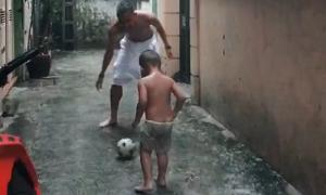 Nghiêm Xuân Tú đá bóng dưới mưa cùng con trai ba tuổi