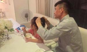 Công Vinh ân cần buộc tóc cho con gái
