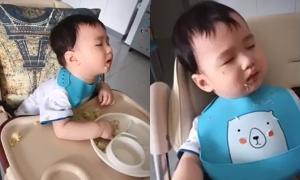 Bé trai vừa ăn vừa ngủ gật