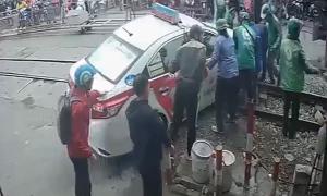 Giải cứu taxi bị mắc kẹt khi cố lao qua rào chắn