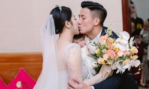 Vợ chồng Bùi Tiến Dũng vừa bế con vừa hôn nhau